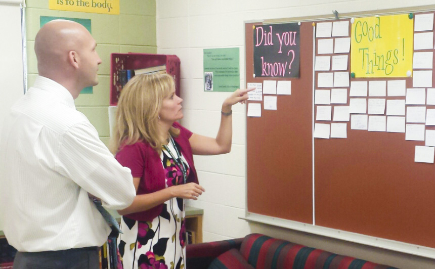 Superintendent Victor Simon and Gower Middle School Principal Tracy Murphy analyze 5Essentials-related highlights on a bulletin board.